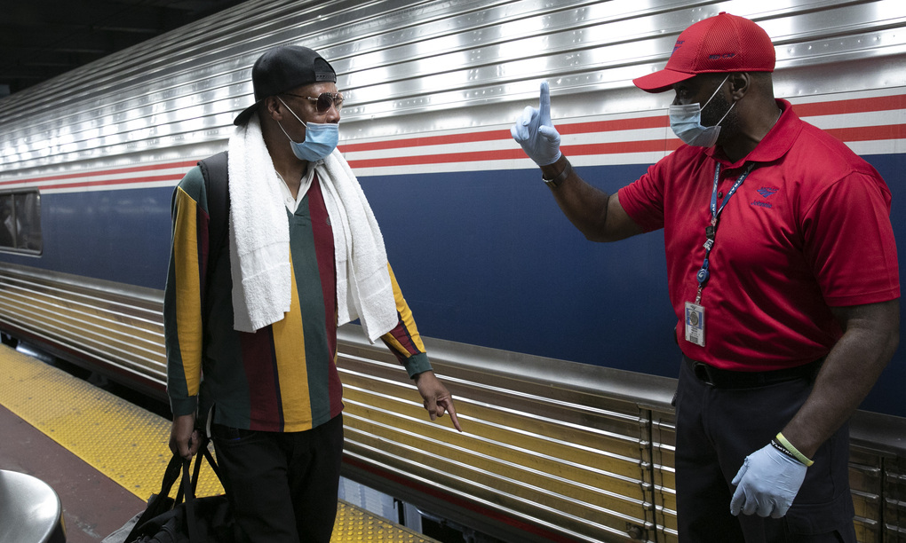 A traveler arriving on a train that originated in Miami gets directions from a porter, right, at Amtrak's Penn Station, on Thursday in New York. Mayor Bill de Blasio is asking travelers from 34 states, including Florida where COVID-19 infection rates are high, to quarantine for 14 days after arriving in the city. (AP Photo/Mark Lennihan)