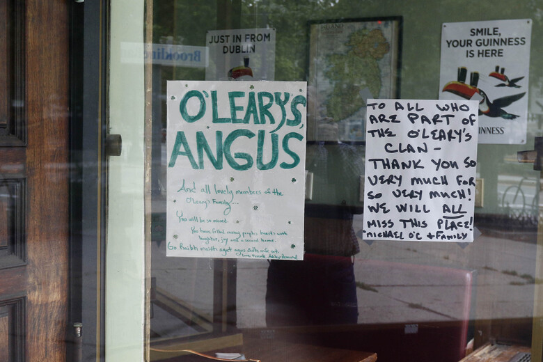 A sign by the owners is posted on a window at the O'Leary's Irish Pub, Tuesday, Aug. 4, 2020, in Brookline, Mass. After being in business for nearly three decades, the pub permanently closed during the coronavirus pandemic. (AP Photo/Bill Sikes)