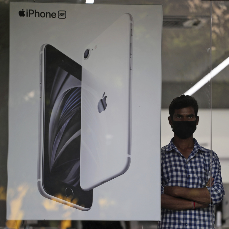 An employee stands by an image of an iPhone displayed at an Apple store in Ahmedabad, India, Saturday, Aug. 1, 2020. Three contract manufacturers for Apple iPhones and South Korea's Samsung have applied for large-scale electronics manufacturing rights in India under a $6.5 billion incentive scheme announced by the government, Technology Minister Ravi Shankar Praad  said Saturday. (AP Photo/Ajit Solanki)