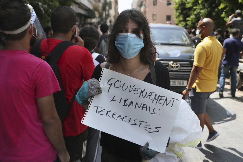 """A woman holds a placard in French that reads, """"Lebanese government terrorists,"""" next to a convoy of French President Emmanuel Macron as he visits the Gemayzeh neighborhood, which suffered extensive damage from an explosion on Tuesday that hit the seaport of Beirut, Lebanon, Thursday, Aug. 6, 2020. (AP Photo/Bilal Hussein)"""