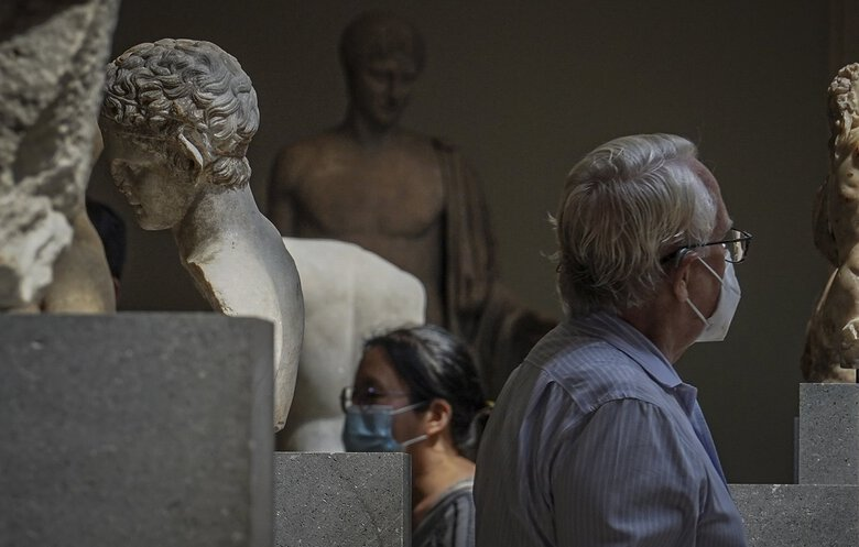 Visitors tour The Metropolitan Museum of Art during a preview in advance of its reopening on Aug. 27, in New York. City museums will institute a range of precautions, including reduced hours, reserved tickets, mask mandates, drastically limiting attendance to a quarter of capacity. (Bebeto Matthews / Associated Press)