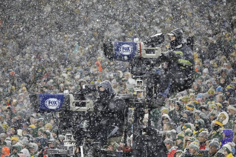Television cameras are seen through the snow during a 2019 game in Green Bay, Wis. (Jeffrey Phelps / Associated Press)