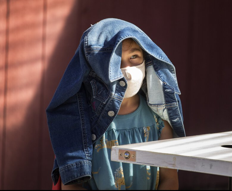 Thursday, Sept. 3, 2020   K-1 class student MeiMei Galligan-Hong uses her jacket to shade herself during as her teacher reads to the class.   (Steve Ringman / The Seattle Times)