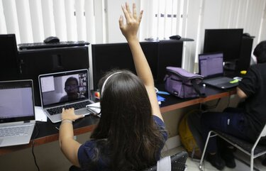 A student raises their hand while attending an online class from a learning center in Miami, Florida, U.S., on Friday, Sept. 4, 2020. In a victory for state education leaders, an appeals court said Monday that Florida's school reopening order did not force students back to campus, nor teachers back into classrooms, and should remain in effect while the lawsuits challenging its constitutionality move through the court system. Photographer: Eva Marie Uzcategui/Bloomberg 775556519