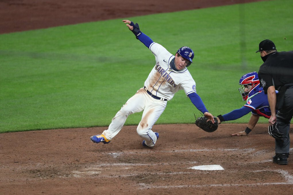 Mariners pinch runner Dylan Moore gets around Texas catcher Jose Trevino to pad the M's lead in the seventh inning after Shed Long, Jr. singles to right field on Sunday in Seattle. (Ken Lambert / The Seattle Times)