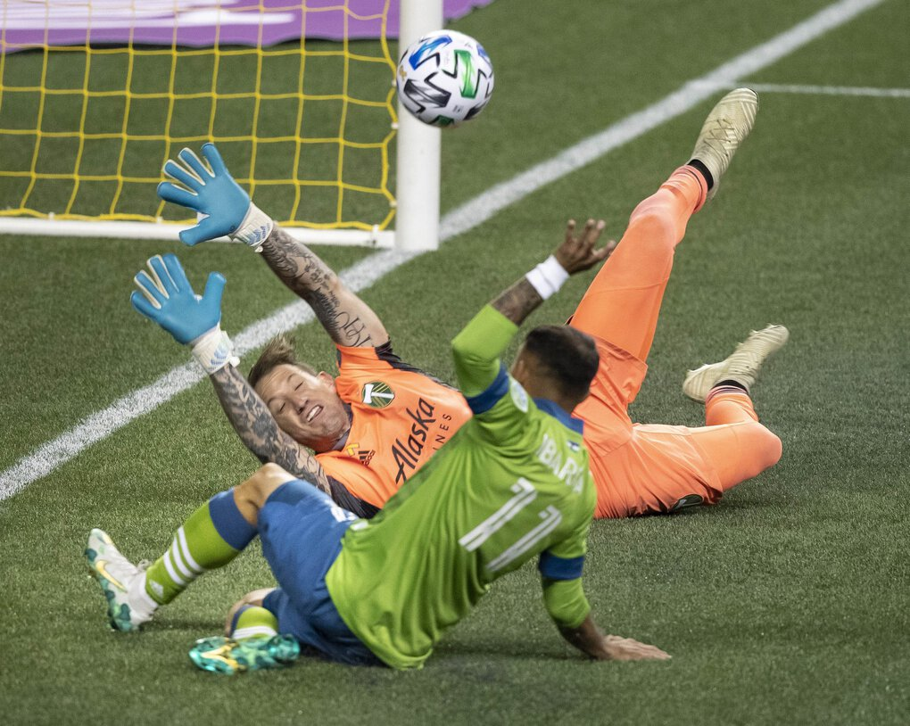 Portland Timbers keeper Steve Clark stops a shot attempt by Miguel Ibarra of the Sounders during Sunday night's match at Century Link Field. (Dean Rutz / The Seattle Times)