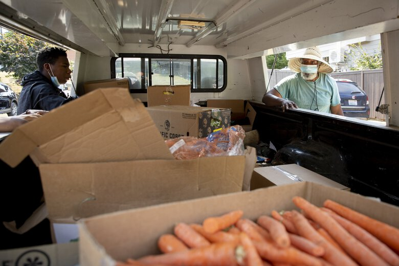 Tommie Willis, right, and his grandson Elijah Prim, left, unload produce from his truck. They brought prepackaged food boxes from the U.S. Department of Agriculture's coronavirus response program as well as produce from Willis's own farm in Duvall. The boxes are from the Farmers to Families program, in which Washington growers received government funds in exchange for packaging surplus produce like potatoes, onions and apples for non-profits to distribute to communities. The church plans to do the free food distribution for the next few weeks on Fridays at 1 p.m. and voter registration every other Saturday starting Sept. 12 from noon to 4 p.m. For more information check their website at gnbchurch.com (Bettina Hansen / The Seattle Times)