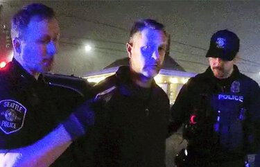 Seattle Police Department Capt. Randal Woolery, center, is arrested during a vice sting on Aurora Avenue last November in this still pulled from police video.