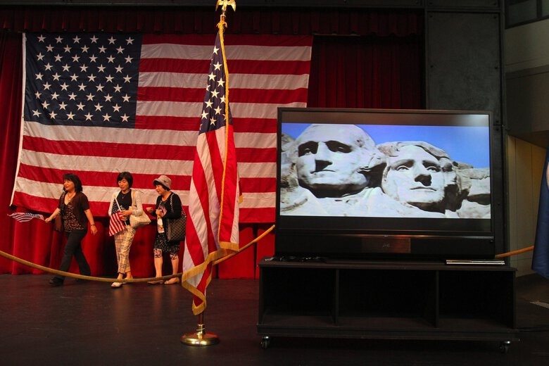 Inside the Armory at Seattle Center in 2014, new citizens had their portraits taken in front of a giant flag as a video screen presented revolving images from across the United States,  including Mount Rushmore with George Washington, left, and Thomas Jefferson. (Alan Berner / The Seattle Times, 2014)