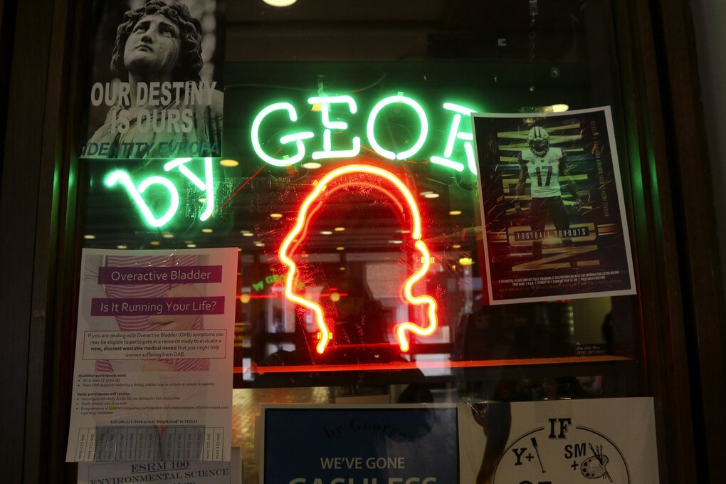 """George Washington's profile shines in neon at the """"by George"""" cafe on the University of Washington's campus. (Alan Berner / The Seattle Times, 2017)"""