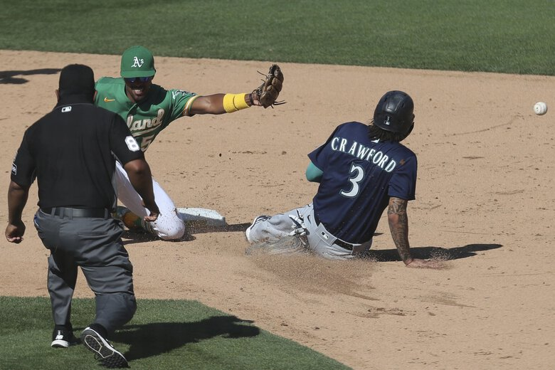 Seattle Mariners' J.P. Crawford (3) steals second base as Oakland Athletics' Tony Kemp waits for the throw during the eighth inning of the first baseball game of a doubleheader Saturday. (Jed Jacobsohn / The Associated Press)