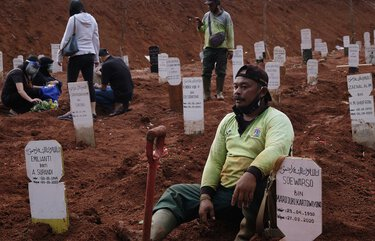An exhausted grave digger takes a break after his stint digging the hardened clay into a grave for a suspected COVID-19 victim at a public cemetery, part of which is reserved for suspected COVID-19 victims on Sept. 27, 2020 in Jakarta, Indonesia. Due to a steady rise in Covid-19 cases, Jakarta is running short on hospital beds, quarantine facilities and now graveyard space. (Ed Wray/Getty Images/TNS) 1781878 1781878