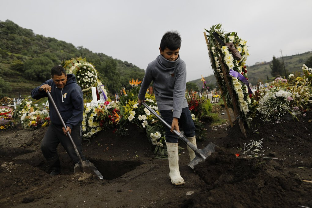 On the outskirts of Mexico City, Lucas, 9, plays around helping his dad, gravedigger Luciano Lopez, left, on Tuesday, Sept. 22, 2020. Lucas came to work with his father since there was no one to stay home with him to attend televised school classes. The two are in a section of the Valle de Chalco Municipal Cemetery which opened early in the new coronavirus pandemic to accommodate the surge in deaths. (Rebecca Blackwell / The Associated Press)
