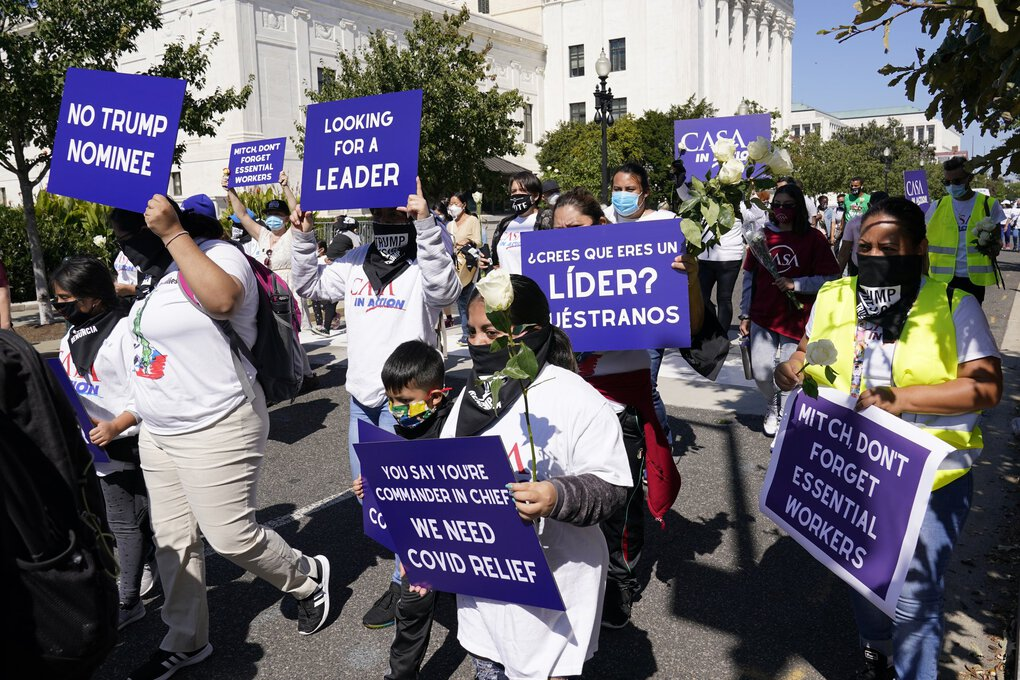 A group of protesters makes their way past the back of the U.S. Supreme Court building in Washington, D.C., on Wednesday. (Susan Walsh / The Associated Press)