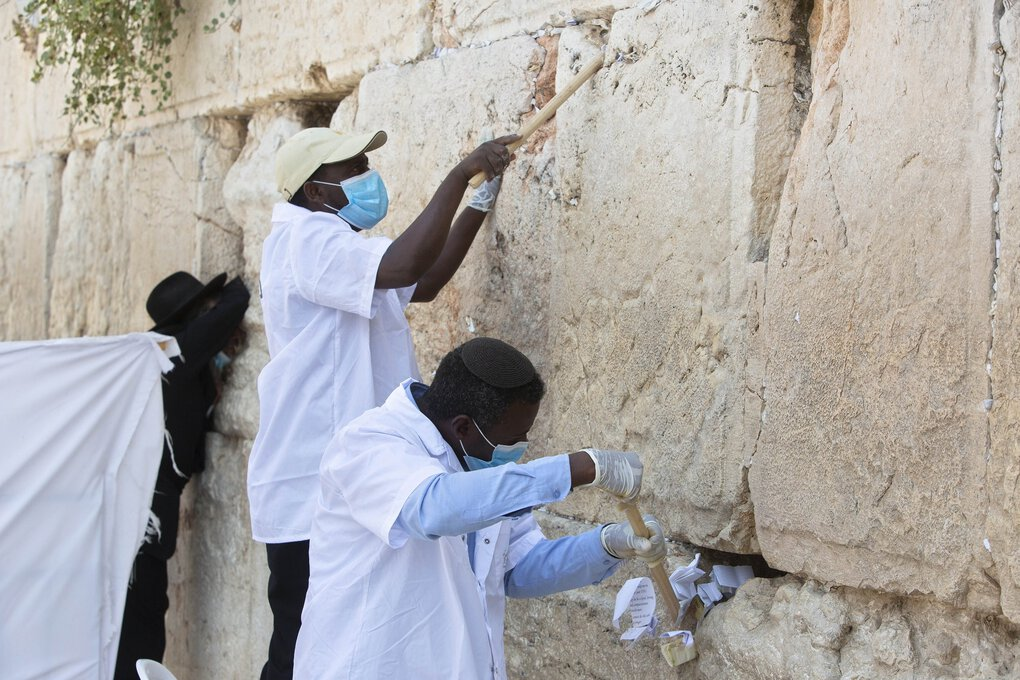Workers remove prayer notes left by visitors from between the stones of the Western Wall, the holiest site where Jews can pray in Jerusalem, on Wednesday. (Sebastian Scheiner / The Associated Press)