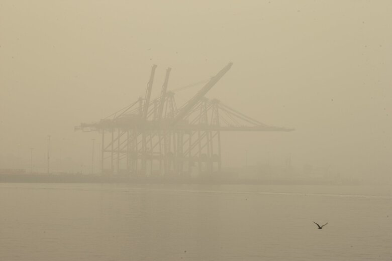 The view of cargo cranes from the Seattle waterfront is obstructed by wildfire smoke lingering in the air on Monday. (Erika Schultz / The Seattle Times)