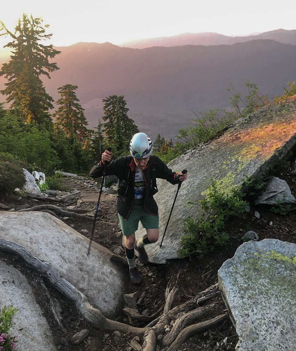 Randall Nordfors climbs through rocks on the Mount Pilchuck Trail in July, 2020, just before sunset, after summiting Glacier Peak that same day.  This photo was taken on his 23rd hour, summiting  his second peak of the day, Mount Pilchuck, 5,324ft, shortly after this photo was taken.  (Aaron Mainer)