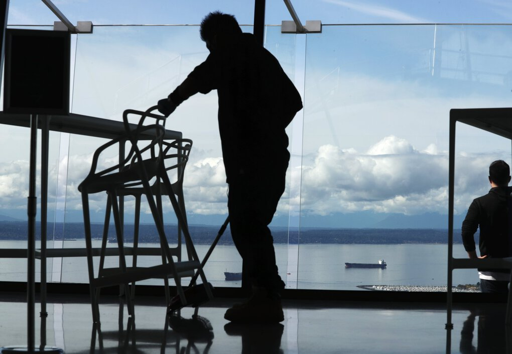 A man sweeps up at the observation area of the Space Needle after smoke and rain gave way to perfect weather Sundaynin Seattle. In the background is Elliott Bay. (Ken Lambert / The Seattle Times)