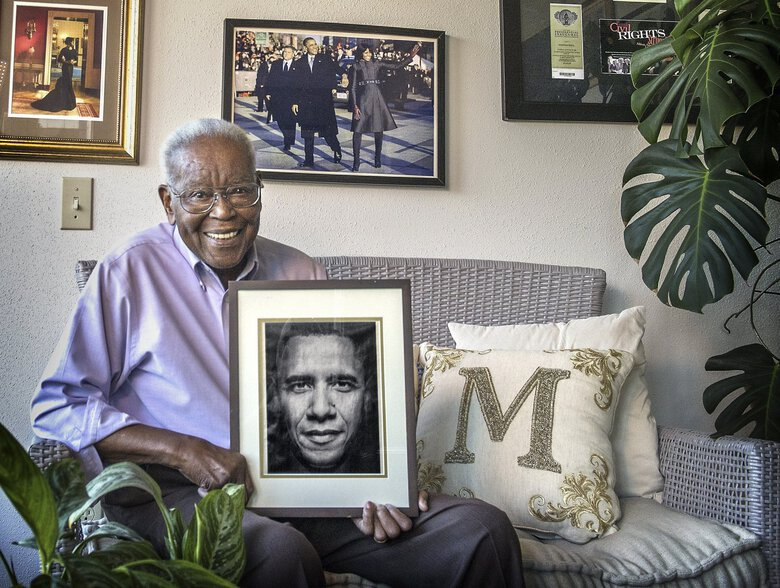 Harold Moss, Tacoma's first black mayor, holds a portrait of President Barack Obama, part of a collection of images and mementos that hang in a room of the Moss household reserved for the 44th president and his family. Moss died Monday night. He was 90. (Dean J. Koepfler / The News Tribune)