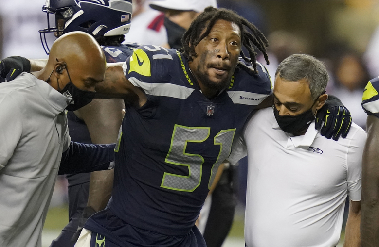 Seattle Seahawks linebacker Bruce Irvin is helped off the field after an injury during the second half of an NFL football game against the New England Patriots, Sunday, Sept. 20, 2020, in Seattle. (AP Photo/Elaine Thompson)