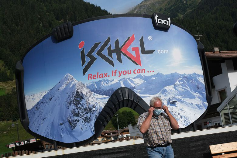 A man removes a protective face mask after photographing himself in front of an advertisement in the shape of ski goggles for the Ischgl ski resort last month Ischgl, Austria. Ischgl became a superspreader locality for coronavirus infections among winter vacationers last March and authorities have pointed to crowded apres-ski venues as a strong contributing factor. At least 28 people died and 6,000 people worldwide have registered with an Austrian lawyer claiming they think they were infected in Ischgl. (Sean Gallup / Getty Images Europe)