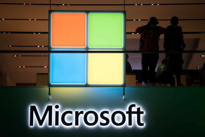Customers stand near the Microsoft logo at a 2017 event in New York. (Mark Kauzlarich / Bloomberg)