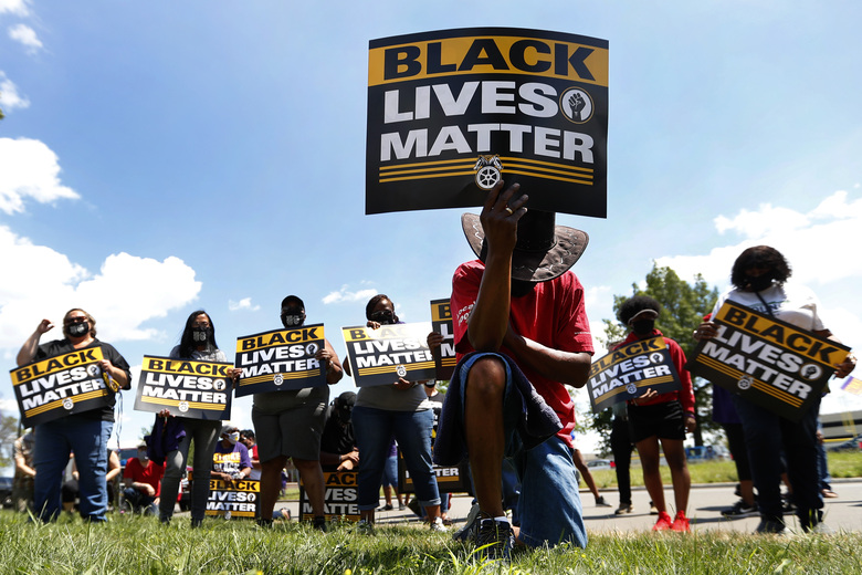 FILE – In this July 20, 2020, file photo, Eddie Perkins takes a knee during a protest rally outside Hartford Nursing & Rehabilitation Center in Detroit. Ahead of Labor Day, major U.S. labor unions say they are considering work stoppages in support of the Black Lives Matter movement. (AP Photo/Paul Sancya, File)