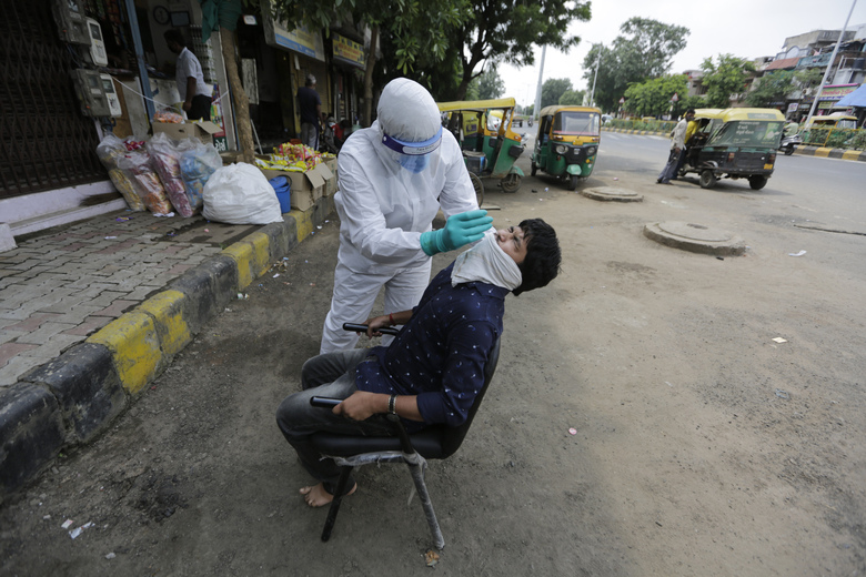 A health worker takes a nasal swab sample to test for COVID-19 in Ahmedabad, India, Tuesday, Sept. 8, 2020. India's coronavirus cases are now the second-highest in the world and only behind the United States. (AP Photo/Ajit Solanki)