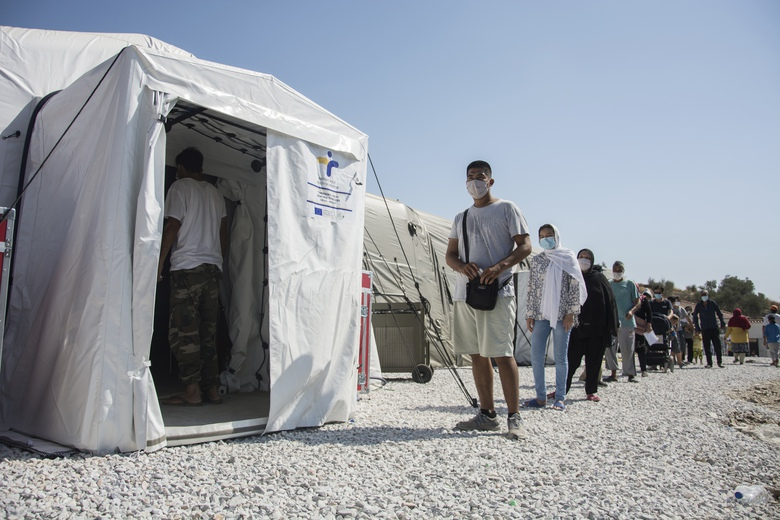 FILE – Migrants wait in a queue to do tests for the new coronavirus in Moria refugee camp on the northeastern Aegean island of Lesbos, Greece, on Friday, Sept. 4, 2020. A major testing and contact-tracing operation at Greece's largest migrant camp on the eastern island of Lesbos has so far detected 17 confirmed cases of COVID-19 infection among the 12,500 people living in the overcrowded facility, officials said on Tuesday, Sept. 8, 2020. (AP Photo/Panagiotis Balaskas, File)
