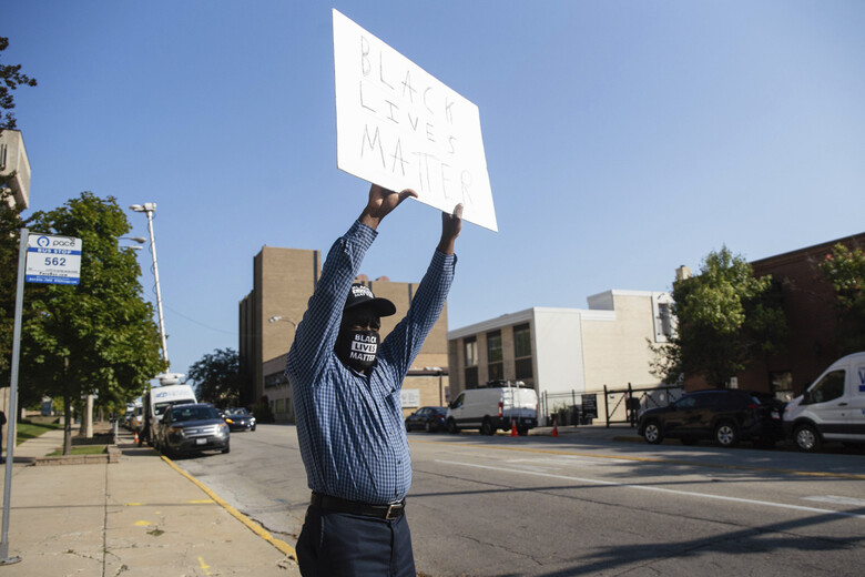 "Alvin Nelson holds a sign that reads ""Black Lives Matter"" outside the Lake County Courthouse in Waukegan, Ill., during Kyle Rittenhouse's second extradition hearing Friday, Sept. 25, 2020. Rittenhouse, accused of killing two protesters days after Jacob Blake was shot by police in Kenosha, Wis., on Friday fought his return to Wisconsin to face homicide charges that could put him in prison for life. (Pat Nabong/Chicago Sun-Times via AP)"