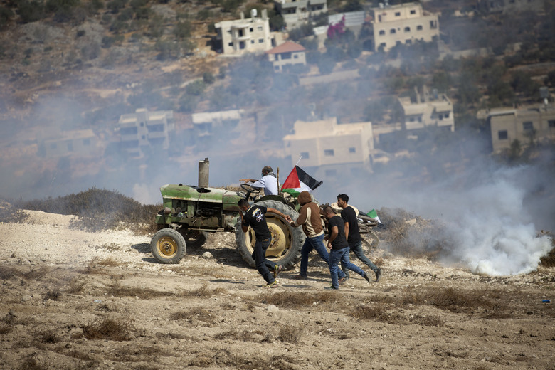 Palestinians run from tear gas fired by Israeli forces during clashes as they protest against Israeli Jewish settlements in Asira al-Qibliya near the West Bank city of Nablus, Friday, Sept. 25, 2020. (AP Photo/Majdi Mohammed)