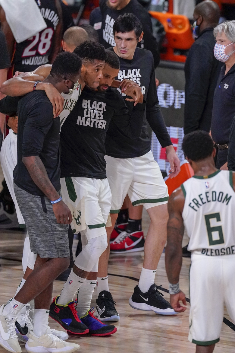 Milwaukee Bucks' Giannis Antetokounmpo is helped off the court after hurting his ankle during the first half of an NBA conference semifinal playoff basketball game against the Miami Heat Sunday, Sept. 6, 2020, in Lake Buena Vista, Fla. (AP Photo/Mark J. Terrill)