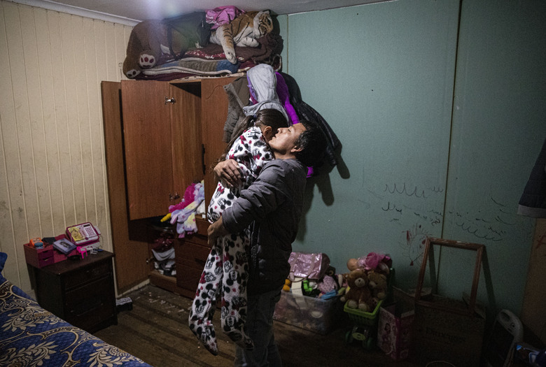 """Jose Collantes hugs his five-year-old daughter Kehity as he puts her to bed for the night at home where they live with Jose's sister in Santiago, Chile, Monday, Aug. 17, 2020, two months after they lost her mother, his wife, to COVID-19. """"I don't want to give up,"""" he said. (AP Photo/Esteban Felix)"""