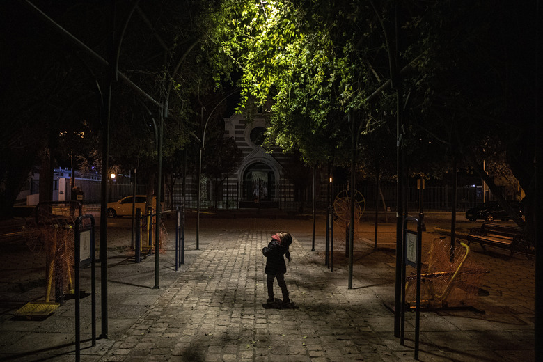 Kehity Collantes, 5, looks up at the light in a park where she came with her father to speak with a family friend in Santiago, Chile, Sunday, Aug. 30, 2020, two months after her mother died of COVID-19. For many pandemic survivors and those who lost loved ones, like the five-year-old Collantes, the tragedy lingers and their lives are never the same. (AP Photo/Esteban Felix)