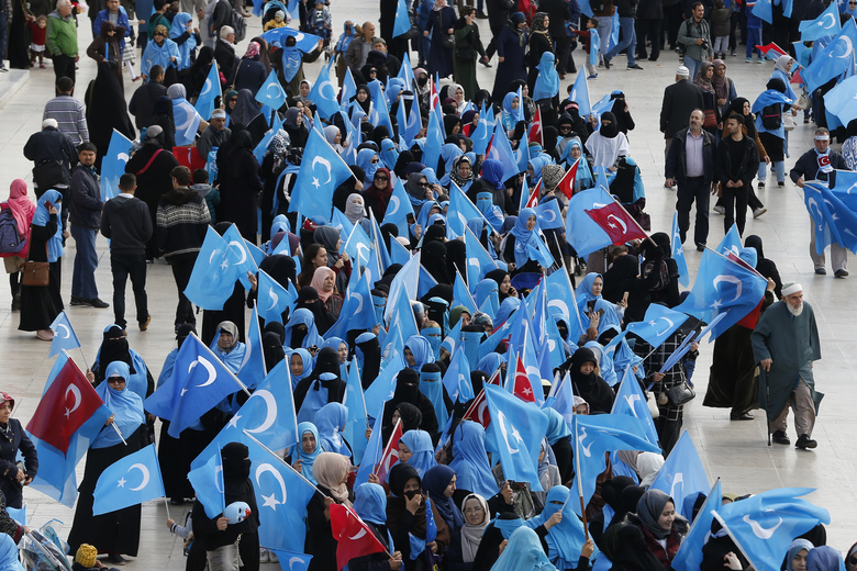 FILE – In this file photo dated Tuesday, Nov. 6, 2018, people from the Uighur community living in Turkey carry flags of what ethnic Uighurs call 'East Turkestan', during a protest in Istanbul, against what they allege is oppression by the Chinese government to Muslim Uighurs in far-western Xinjiang province. The prominent British human rights lawyer Geoffrey Nice is convening an independent tribunal in London with public hearings in 2021, to look into the Chinese government's alleged rights abuses against the Uighur Muslim minority in the far western province of Xinjiang. (AP Photo/Lefteris Pitarakis, FILE)