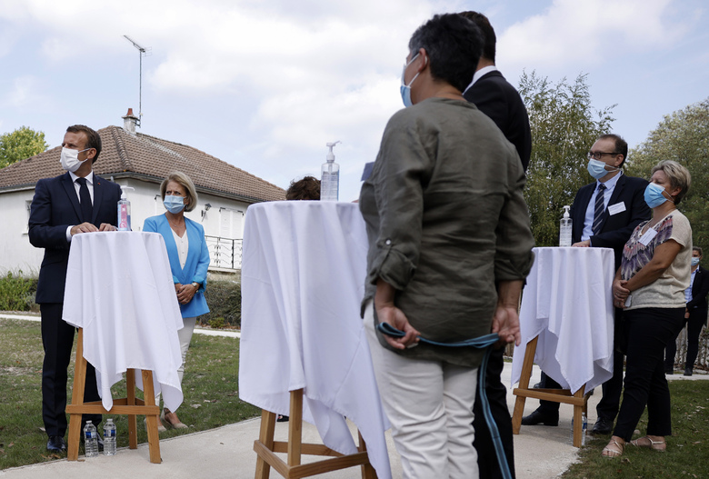 French President Emmanuel Macron, left, and Junior Minister of Autonomy Brigitte Bourguignon, 2nd left, meet healthcare workers at the 'La Bonne Eure' nursing home in Bracieux, central France, Tuesday, Sept. 22, 2020. For the first time in months, virus infections and deaths in French nursing homes are on the rise again. (Yoan Valat/Pool Photo via AP)