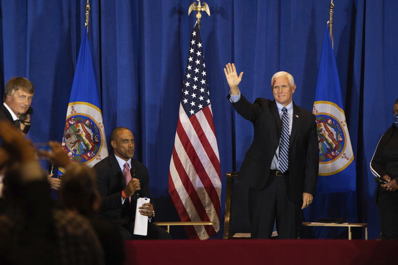 "Vice President Mike Pence waves to an audience as he arrives at a ""Cops for Trump"" listening session inside of the Intercontinental Hotel at Minneapolis- St. Paul International Airport on Thursday, Sept. 24, 2020. (Evan Frost/Minnesota Public Radio via AP)"
