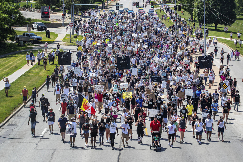 FILE – In this Sunday, June 7, 2020, file photo, marchers walk along a street during a rally to remember James Scurlock, in Omaha, Neb. Scurlock, a Black man, was fatally shot by white bar owner Jake Gardner during an Omaha protest over George Floyd's death. Gardner will be charged with manslaughter and several other charges. (Chris Machian/Omaha World-Herald via AP, File)