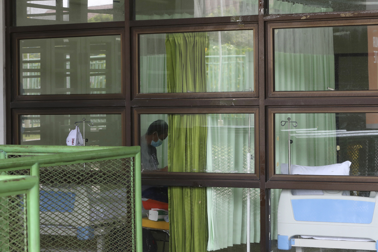 A patient sits inside a quarantine facility for people showing symptoms of the COVID-19 amid the coronavirus outbreak at Patriot Candrabhaga stadium in Bekasi on the outskirts of Jakarta, Indonesia, Tuesday, Sept. 22, 2020. (AP Photo/Achmad Ibrahim)