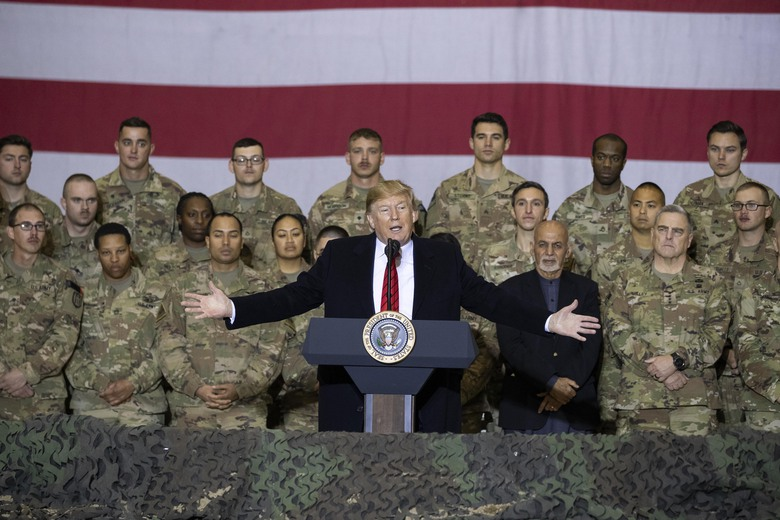 "FILE – In this Nov. 28, 2019 file photo, President Donald Trump, center, with Afghan President Ashraf Ghani and Joint Chiefs Chairman Gen. Mark Milley, behind him at right, addresses members of the military during a surprise Thanksgiving Day visit at Bagram Air Field, Afghanistan. During his election campaign four years ago, Trump vowed to bring all troops home from ""endless wars."" In recent months he's only increased the pressure, working to fulfill his campaign promise and get forces home before Election Day. (AP Photo/Alex Brandon, File)"