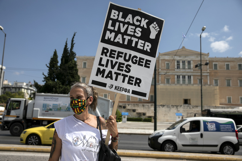 A protester raises a placard during a rally in support of the migrants on the island of Lesbos, in Athens, Saturday, Sep. 12, 2020. Thousands of asylum-seekers spent a fourth night sleeping in the open on the Greek island of Lesbos, after successive fires destroyed the notoriously overcrowded Moria camp during a coronavirus lockdown. (AP Photo/Yorgos Karahalis)