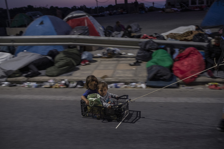 Two children from Afghanistan inside a crate are pulled by a man on the road that refugees and migrants from the fire-destroyed Moria camp are sheltered, on the island of Lesbos, Greece, Friday, Sept. 11, 2020. (AP Photo/Petros Giannakouris)