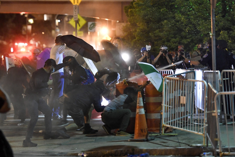 Police spray an irritant at demonstrators outside the Public Safety Building in Rochester, N.Y., Thursday, Sept. 3, 2020. Seven police officers involved in the suffocation death of Daniel Prude in Rochester were suspended Thursday by the city's mayor, who said she was misled for months about the circumstances of the fatal encounter.(AP Photo/Adrian Kraus)