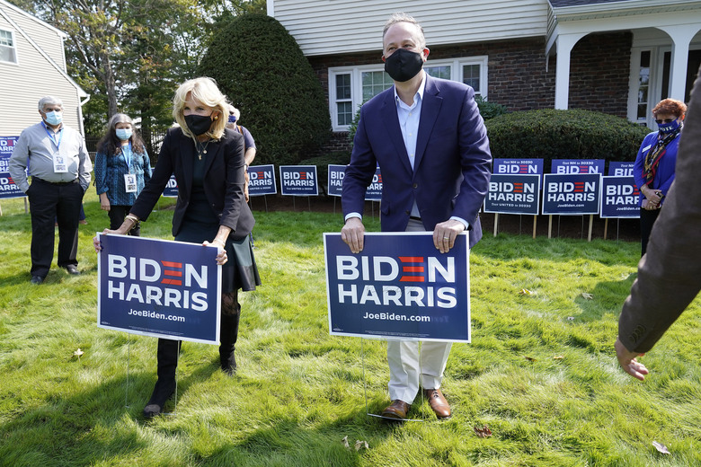 Jill Biden, front left, wife of Democratic presidential candidate former vice president Joe Biden, and Doug Emhoff, center, husband of Democratic vice presidential candidate Sen. Kamala Harris, D-Calif., place campaign placards into the ground during a campaign stop, Wednesday, Sept. 16, 2020, in Manchester, N.H. (AP Photo/Steven Senne)