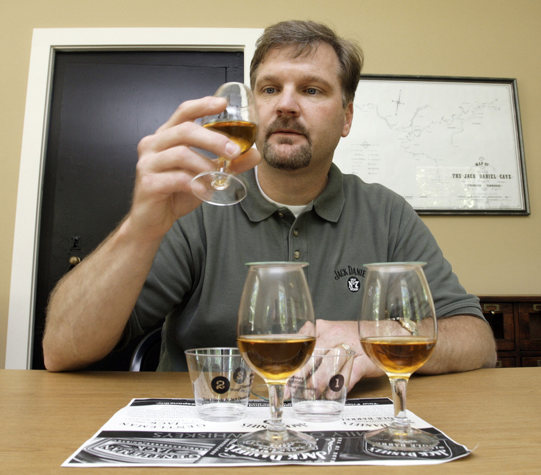 FILE – In this May 20, 2009 file photo Jeff Arnett, the master distiller at the Jack Daniel Distillery in Lynchburg, Tenn., tests glasses of whiskey during a taste test at the distillery. After 12 years of leading production of the powerhouse Jack Daniel's whiskey brand, Arnett is stepping down as master distiller at the Tennessee distillery, the company announced Thursday, Sept. 3, 2020.  (AP Photo/Mark Humphrey, File)