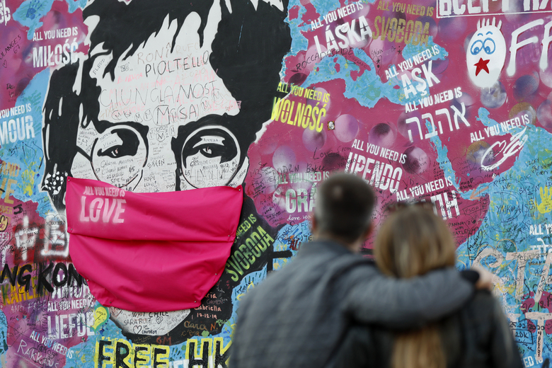 "FILE – A couple look at the ""Lennon Wall"" with a face mask attached to the image of John Lennon, in Prague, Czech Republic, on April 6, 2020. Like so many other events in the year of coronavirus, an annual tribute to John Lennon held in its adopted city of New York will go online. The five-hour event will be streamed for free on Lennon's birthday, October 9, starting at 7 p.m. Eastern time on the LennonTribute.org website. It will feature recorded performances from Patti Smith, Rosanne Cash, Natalie Merchant, Jackson Browne, Jorma Kaukonen and others. (AP Photo/Petr David Josek)"