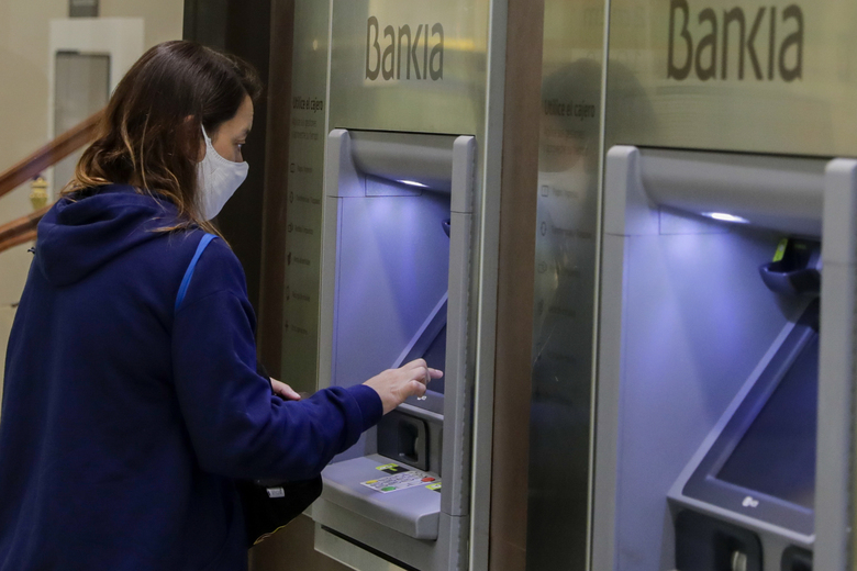 A woman uses an ATM cash point machine at a branch of the Bankia bank in Madrid, Spain, Friday, Sept. 18, 2020. Two of Spain's biggest banks have announced their merger, pushed together by a need to weather tough economic times that likely will cost thousands of jobs. The tie-up between CaixaBank and Bankia will create the largest lender in the country, with assets of more than 664 billion euros ($787 billion). (AP Photo/Manu Fernandez)