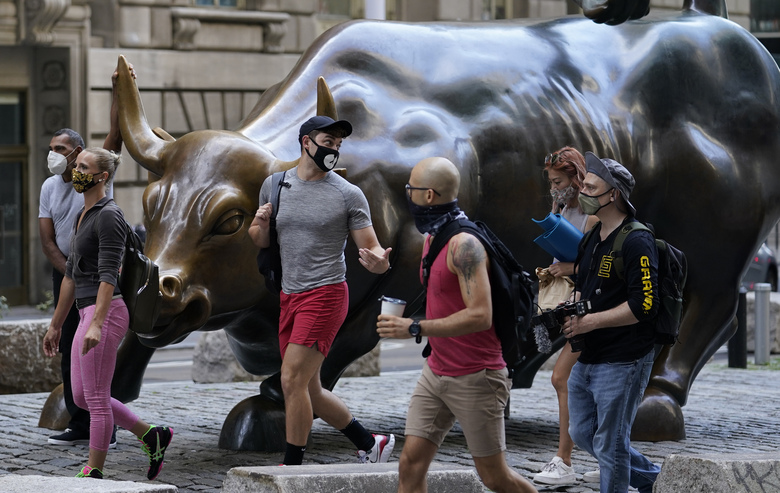 FILE – In this Tuesday, Sept. 8, 2020, file photo, people wearing masks pass the Charging Bull statue in New York's financial district. Wall Street is steadying itself Wednesday following its first three-day losing streak in nearly three months, as the bloodletting for big technology stocks comes to at least a temporary halt. (AP Photo/Mark Lennihan, File)