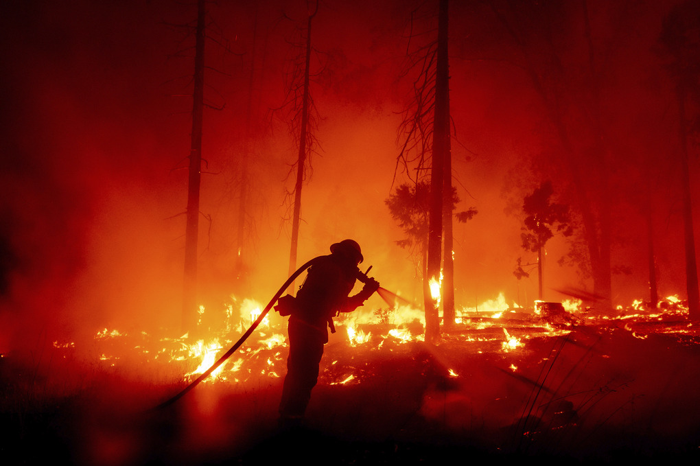 A firefighter battles the Creek Fire on Sept. 7 as it threatens homes in Madera County, Calif. This year's fires have taxed the human, mechanical and financial resources of the nation's wildfire fighting forces to a degree that few past blazes did. And half of the fire season is yet to come. (AP Photo/Noah Berger, file)