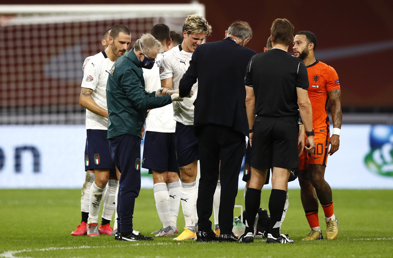 Italy's Nicolo Zaniolo, center, grimaces in pain after being injured during the UEFA Nations League soccer match between The Netherlands and Italy at the Johan Cruijff ArenA in Amsterdam, Netherlands, Monday, Sept. 7, 2020. (AP Photo/Peter Dejong)